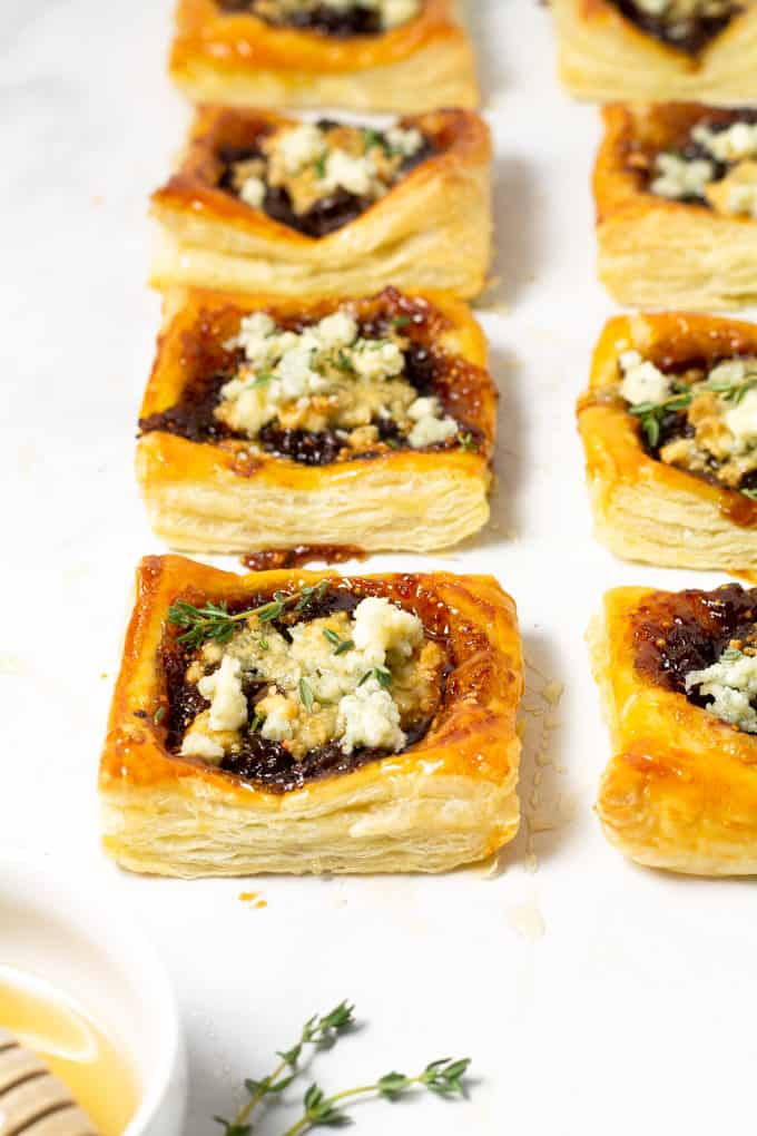 Close up shot of a white counter top with caramelized onion tarts on it