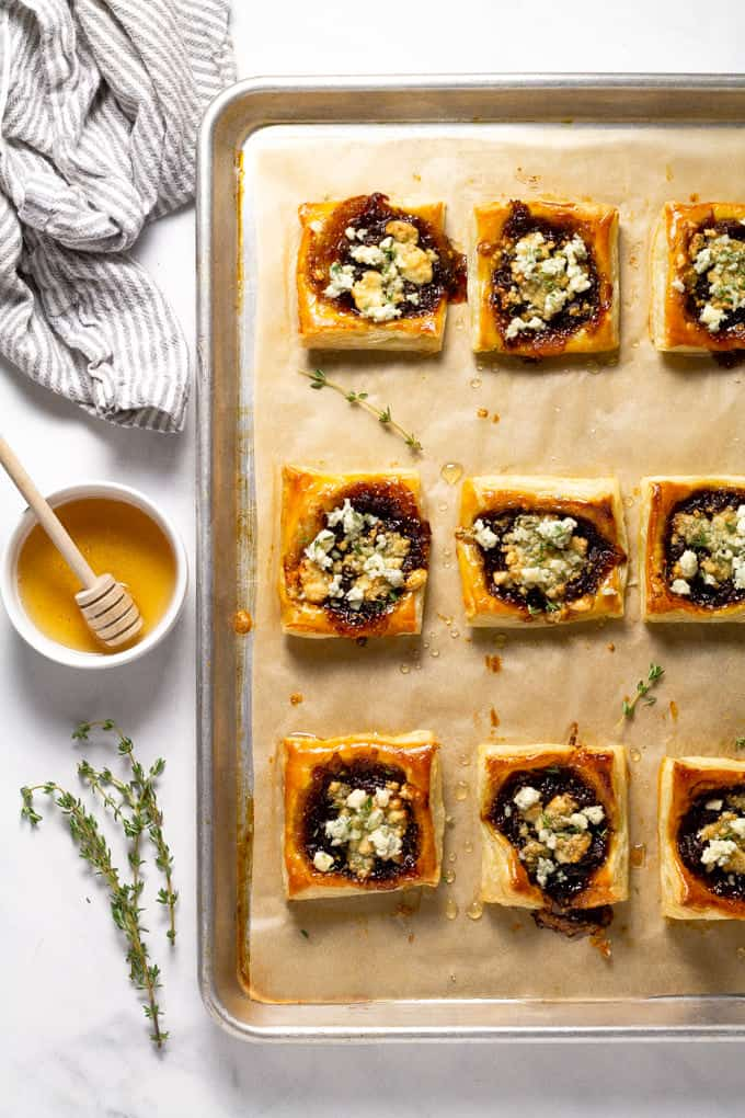 Parchment lined baking sheet filled with freshly baked caramelized onion tarts