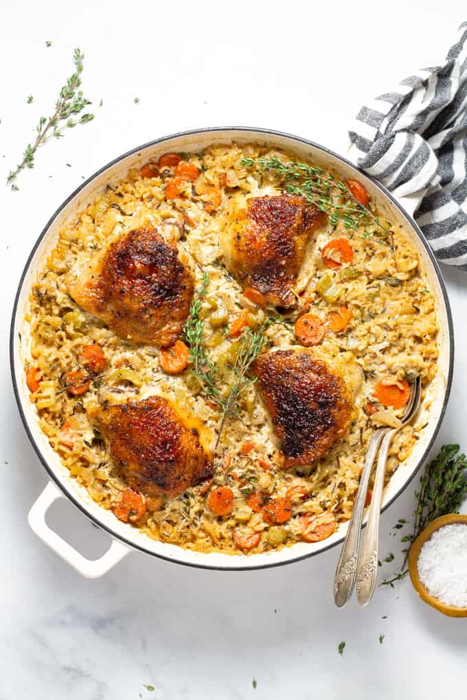 Overhead shot of a pan filled with chicken and rice casserole garnished with sprigs of fresh thyme