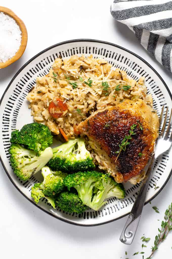 Overhead shot of a plate filled with chicken and rice casserole along with sauteed broccoli