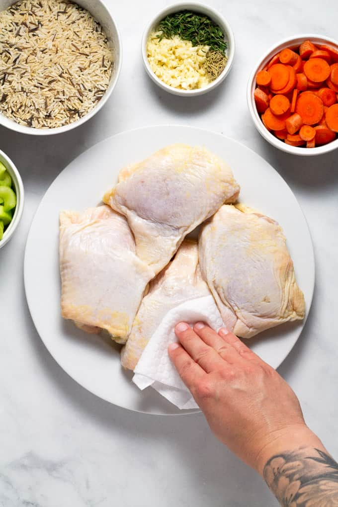 Chicken thighs on a white plate with a hand using a paper towel to dry the chicken skins