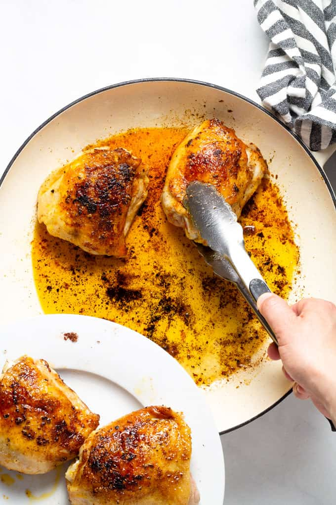 Tongs removing seared chicken thighs from a large pan