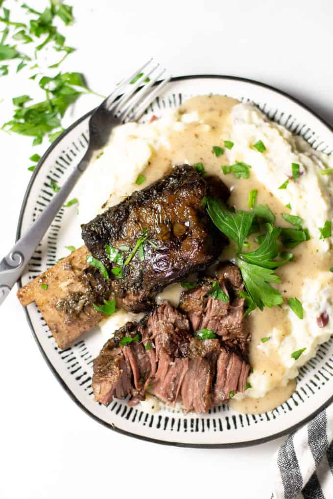 Overhead shot of a white plate filled with homemade garlic mashed potatoes and beef short ribs