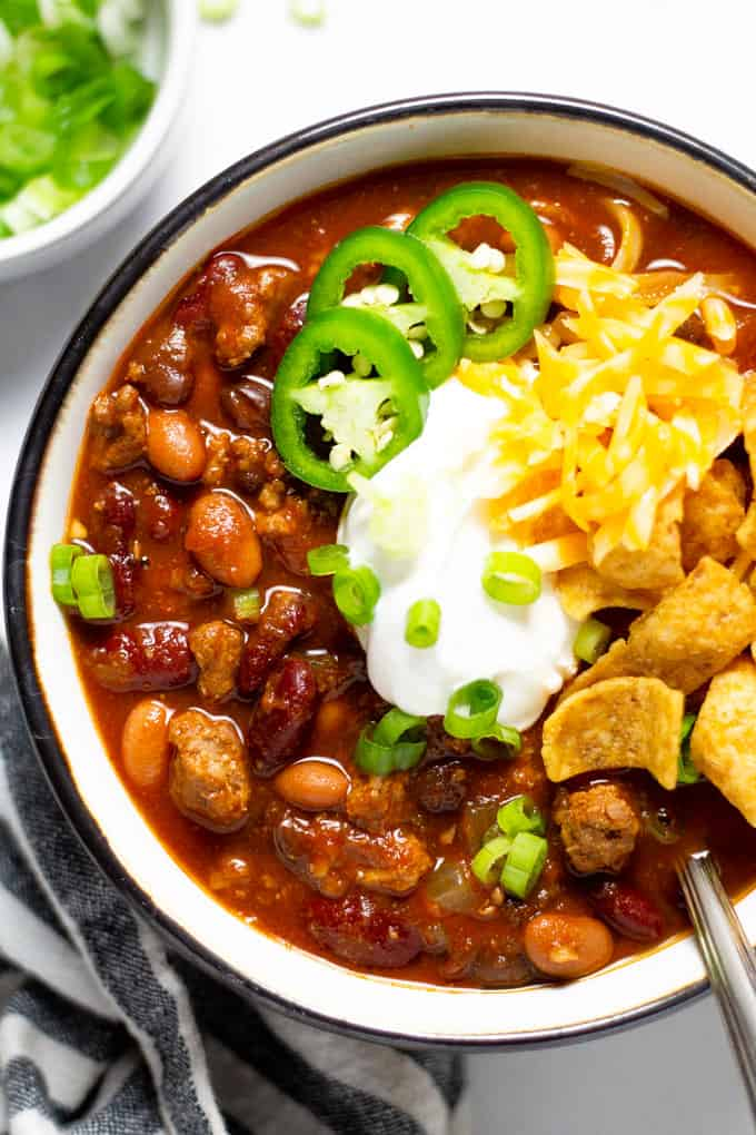 Overhead shot of a bowl of homemade slow cooker turkey chili topped with sour cream