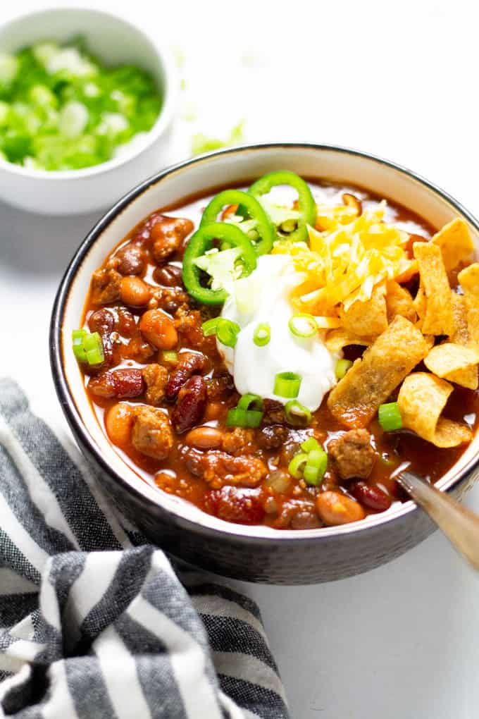 A close up shot of a bowl of slow cooker turkey chili garnished with sour cream