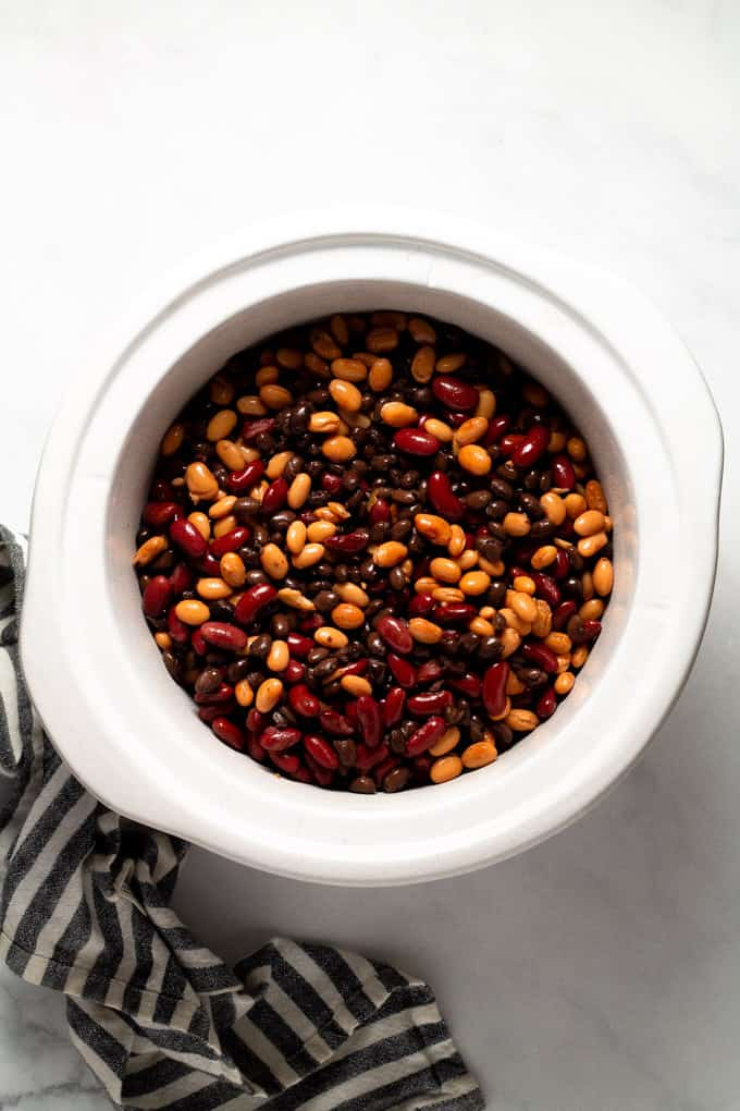 A white crock pot insert filled with beans