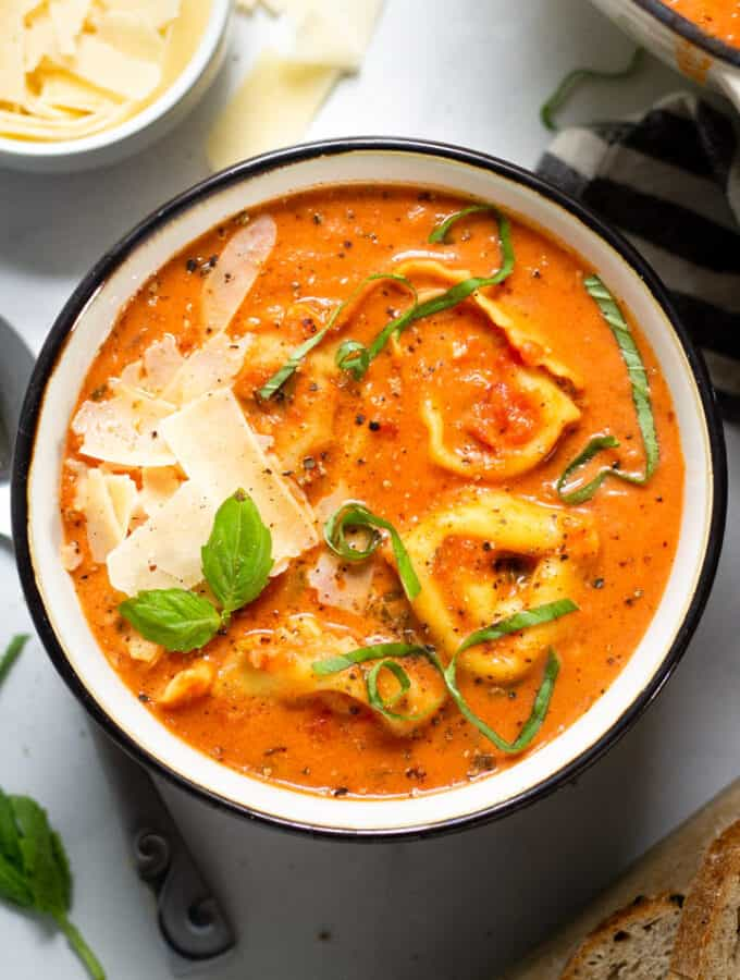 Overhead shot of a bowl of tomato tortellini soup garnished with fresh basil and Parmesan cheese