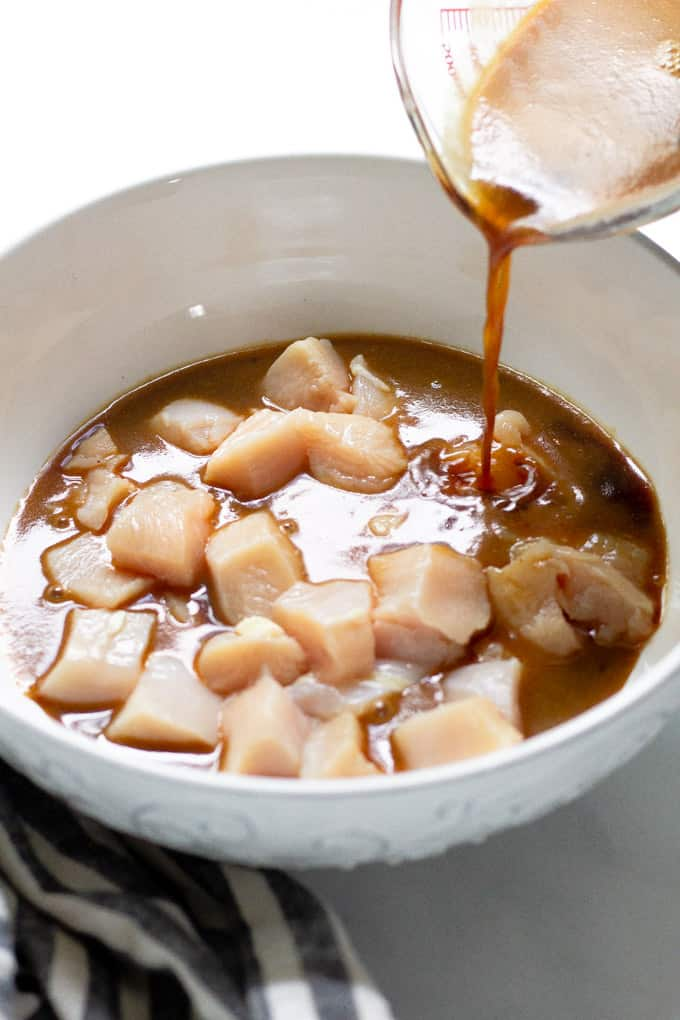 White bowl filled with diced chicken with marinade being poured over it.