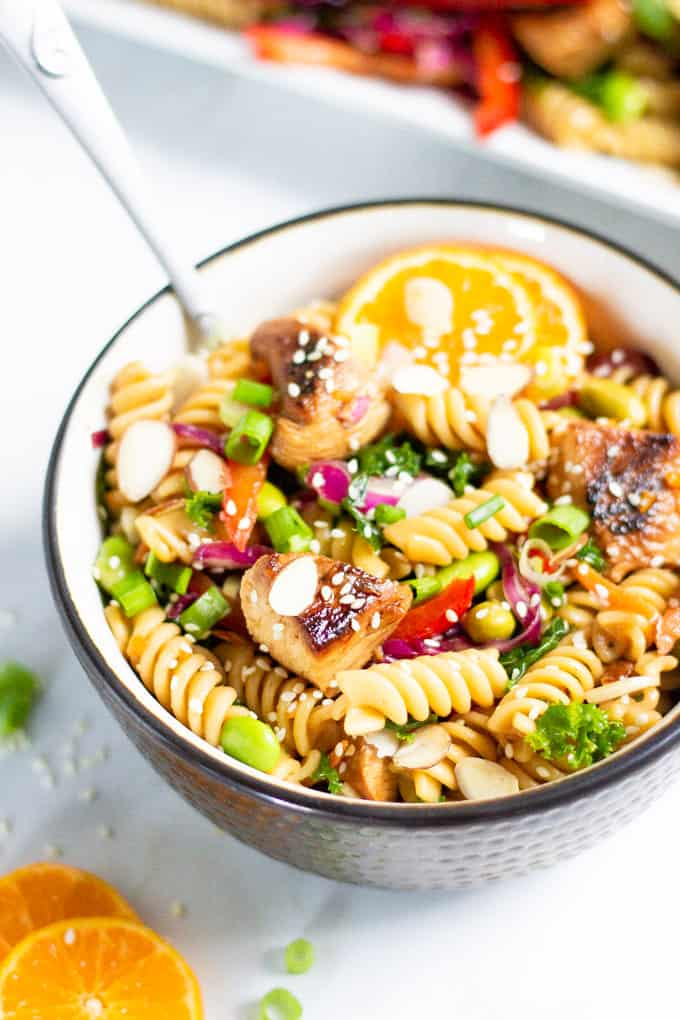 Black and white bowl filled with Asian Chicken Pasta Salad garnished with sesame seeds