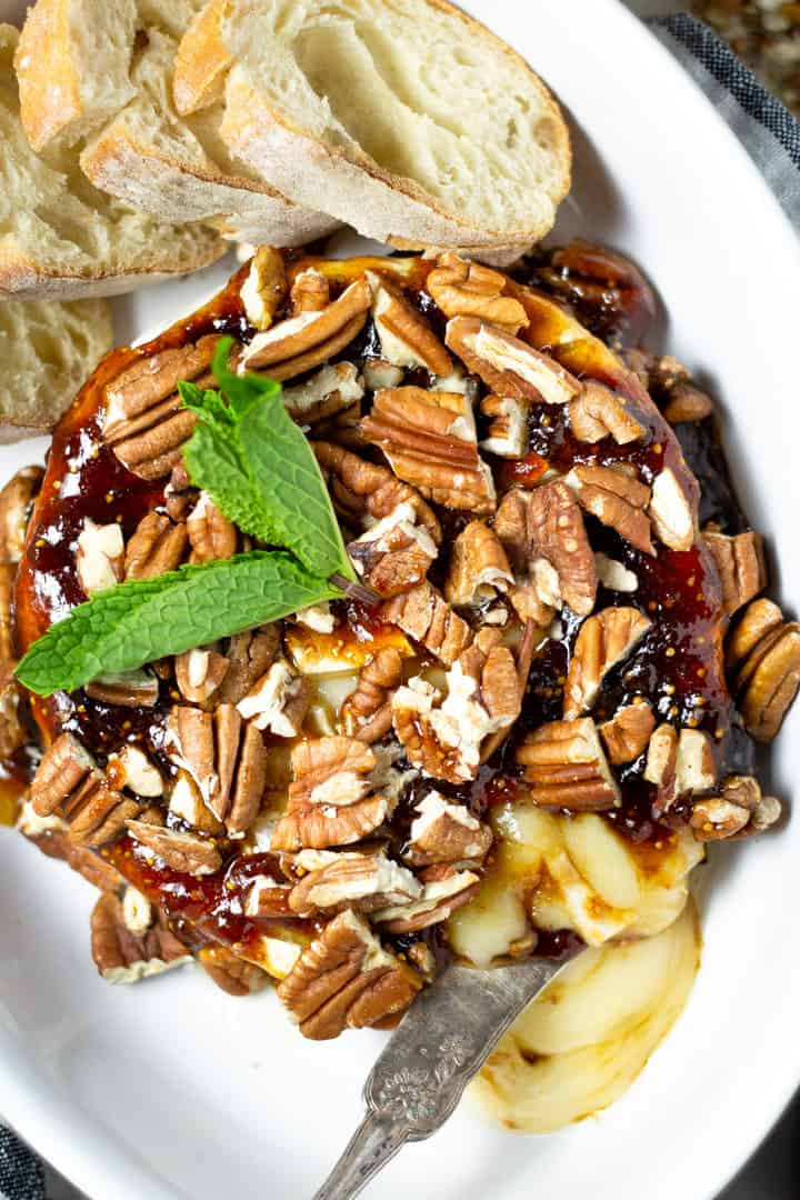 Overhead shot of baked brie topped with fig jam and pecans in a large white serving dish