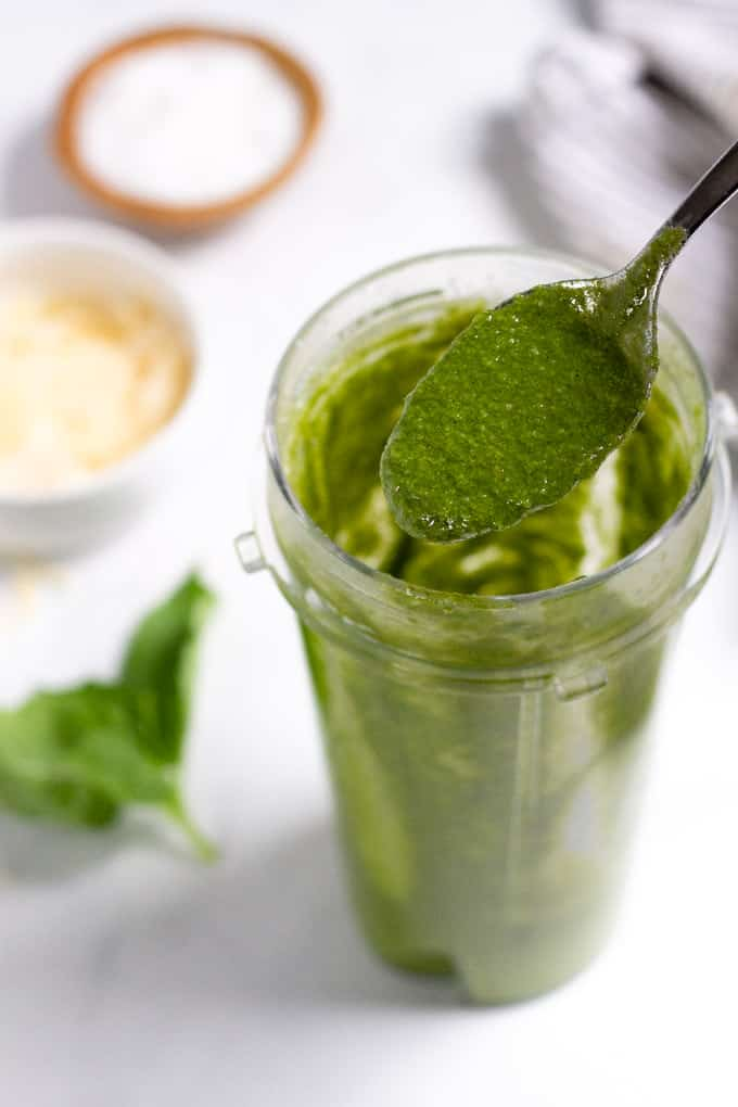 A spoon scooping homemade basil pesto out of a small smoothie container