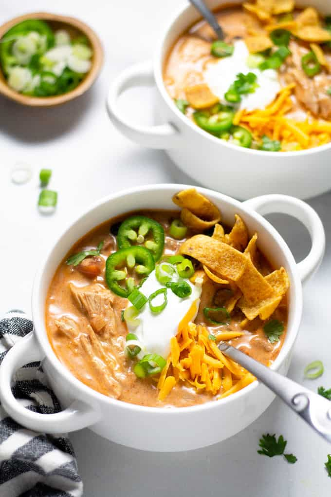Close up shot of a white bowl filled with slow cooker chicken chili garnished with sour cream and green onions