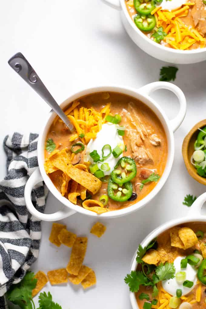 Overhead shot of a white bowl filled with slow cooker chicken chili garnished with sour cream and green onions