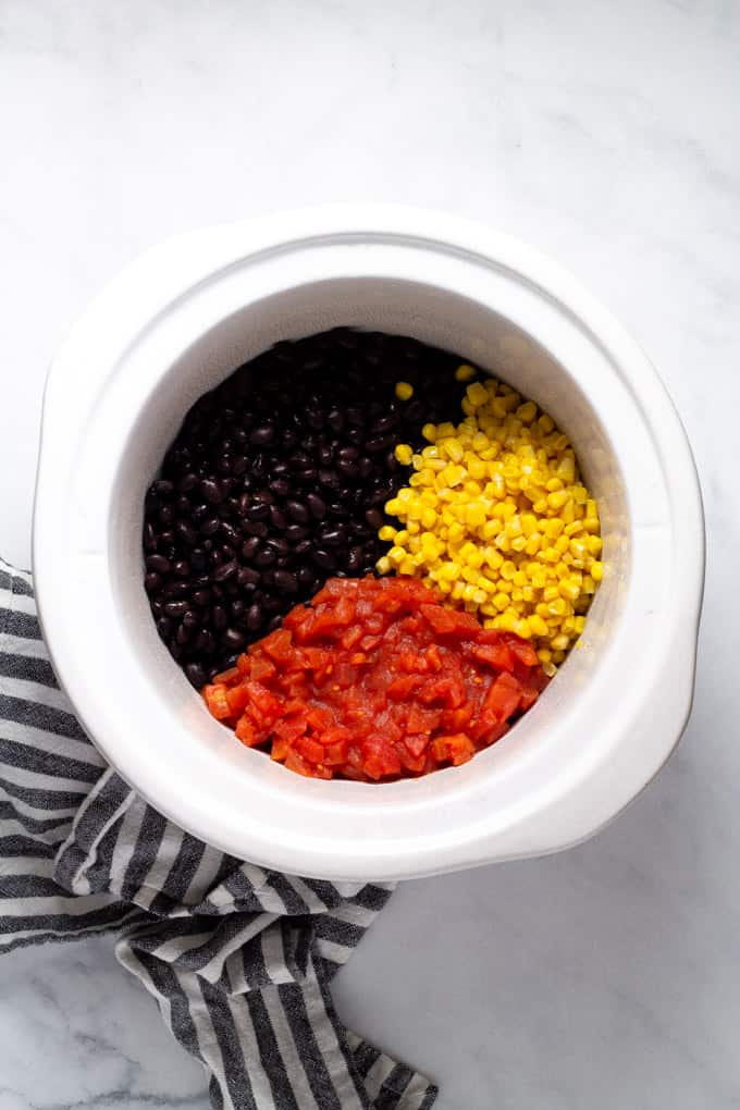 White crock pot insert filled with black beans corn and diced tomatoes