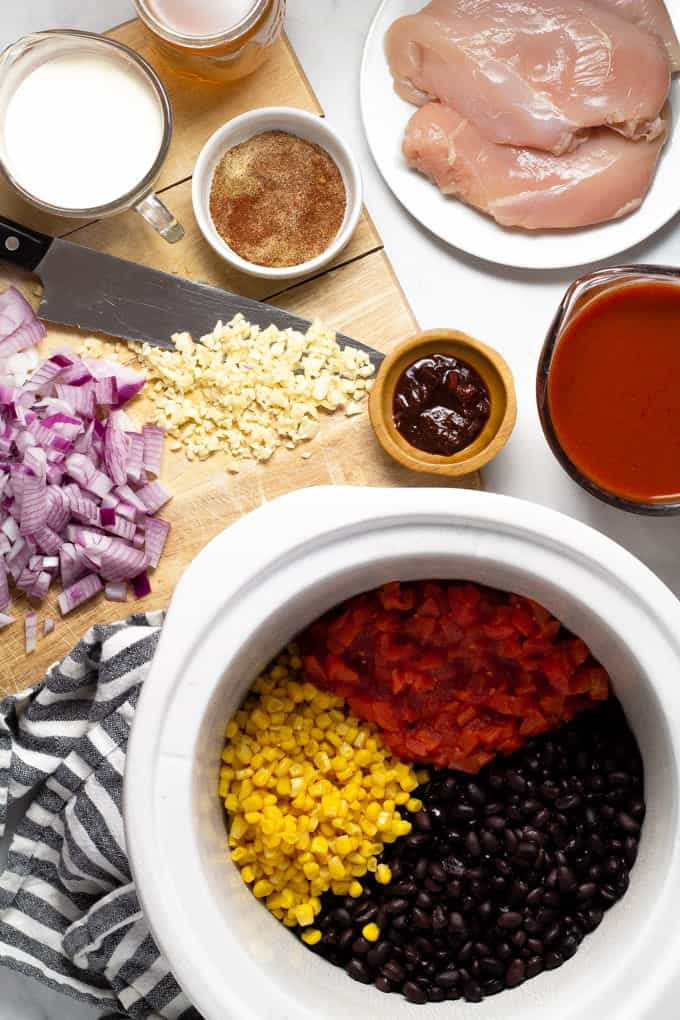 White marble counter top with ingredients to make slow cooker chicken enchilada soup
