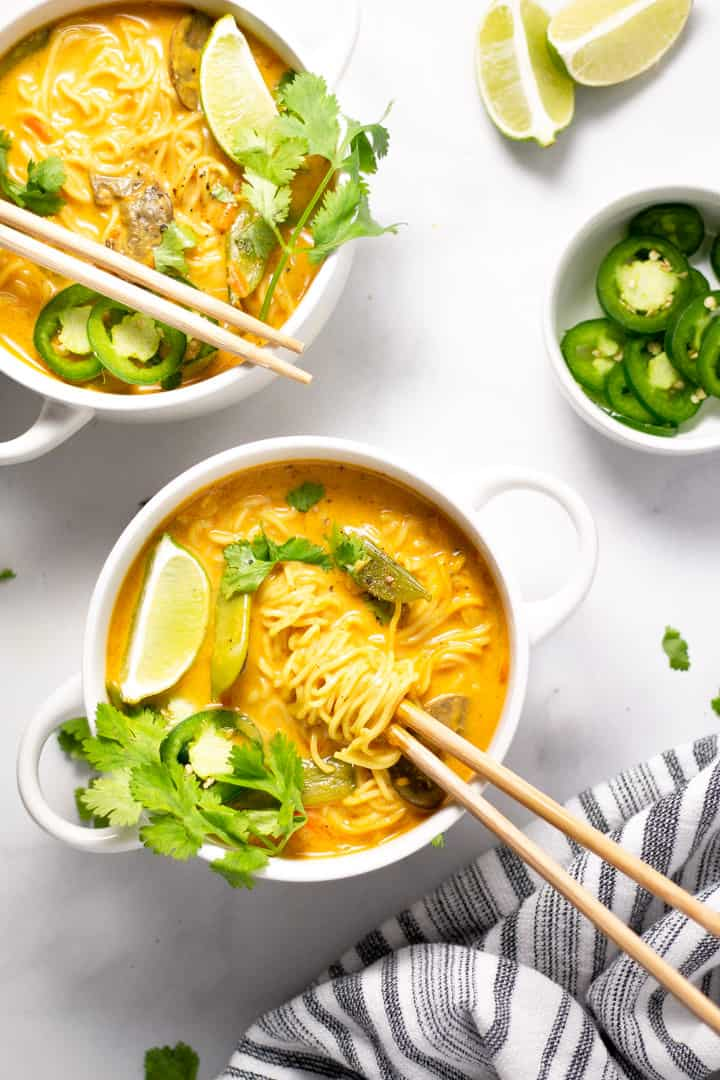 Overhead shot of two bowls of curry ramen noodle soup garnished with fresh cilantro