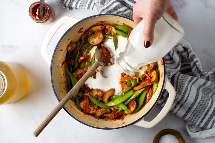 Overhead shot of a white dutch oven filled with curried veggies with coconut milk being added