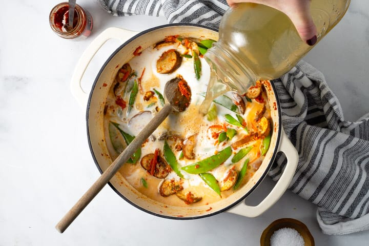 Overhead shot of a white dutch oven filled with curried vegetables with vegetable broth being added