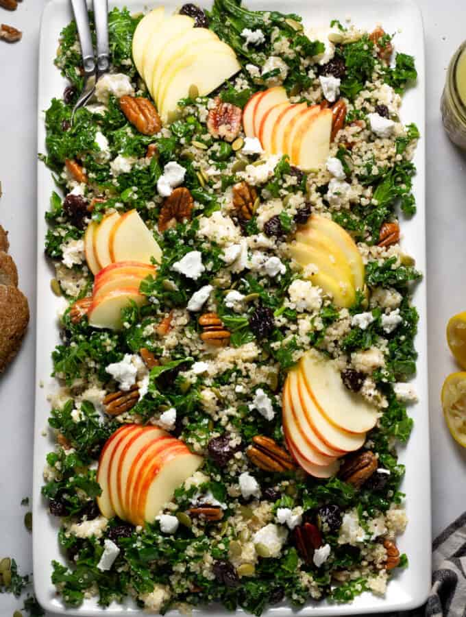 Overhead shot of a large white platter filled with fall harvest salad tossed in cider Dijon vinaigrette