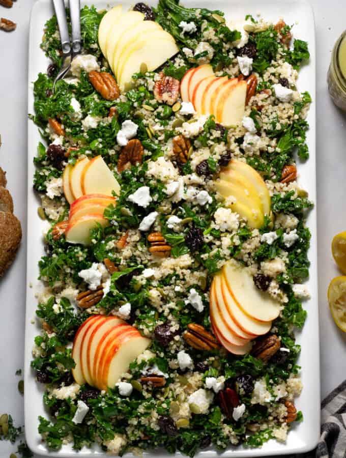 Overhead shot of a large white platter filled with fall harvest salad tossed in cider Dijon vinaigrette