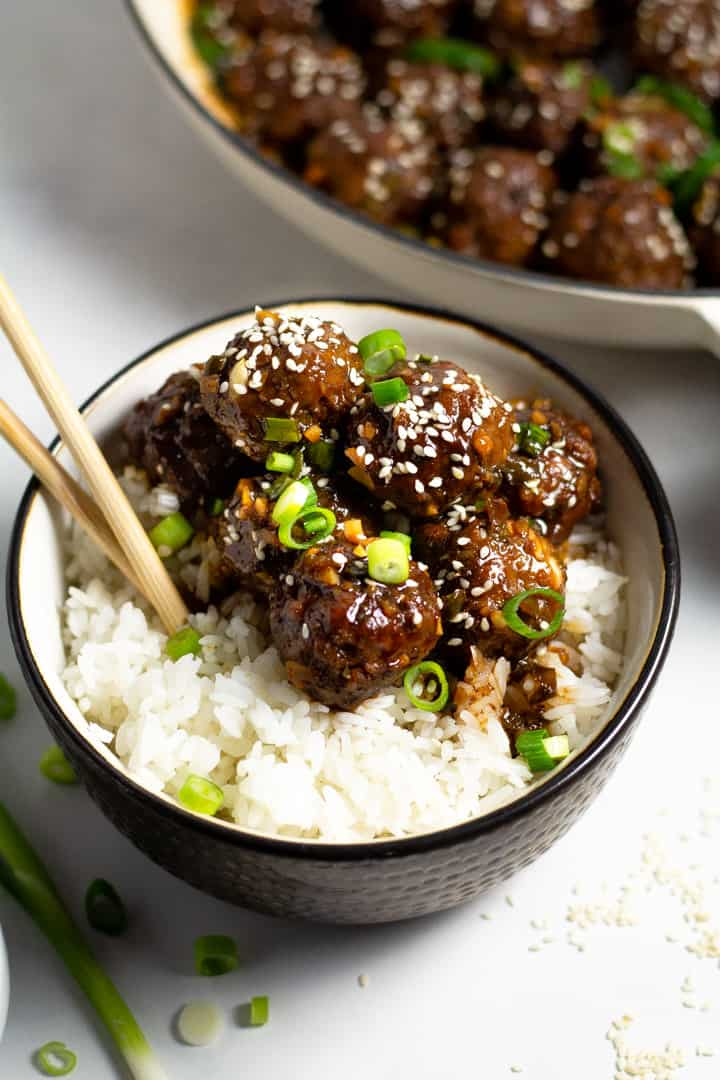 Korean beef meatballs on a bed of rice in a black and white bowl