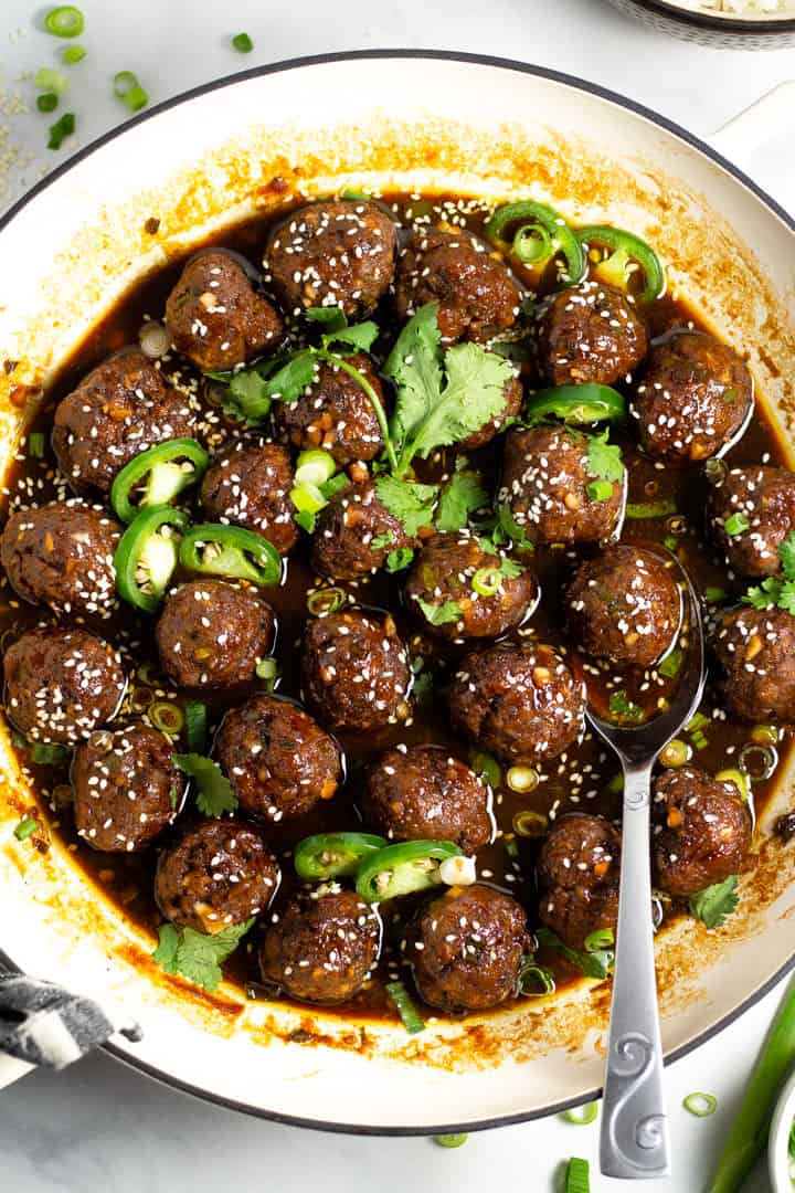 Overhead shot of a white pan filled with Korean beef meatballs garnished with fresh chopped cilantro