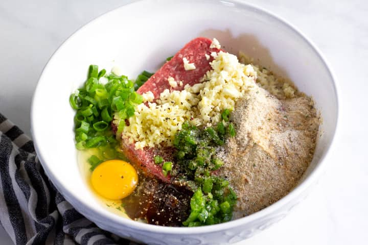 White bowl filled with ingredients to make Korean beef meatballs