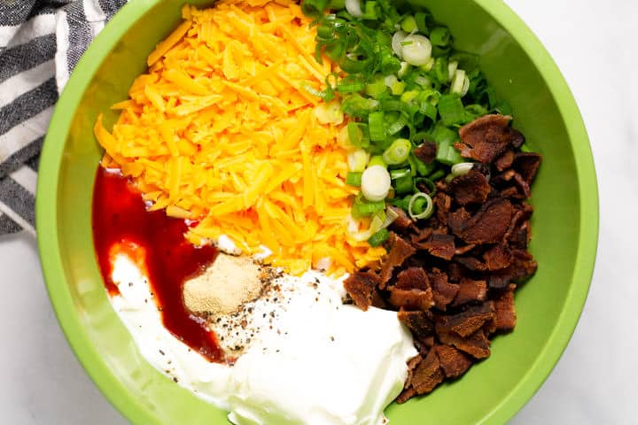 Large green bowl filled with ingredients to make loaded baked potato dip