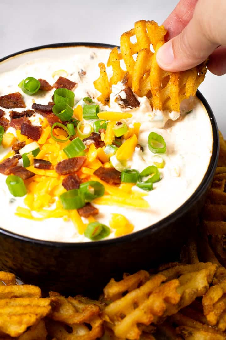 Close up shot of a big bowl filled with loaded baked potato dip with two waffle fries being dipped in it