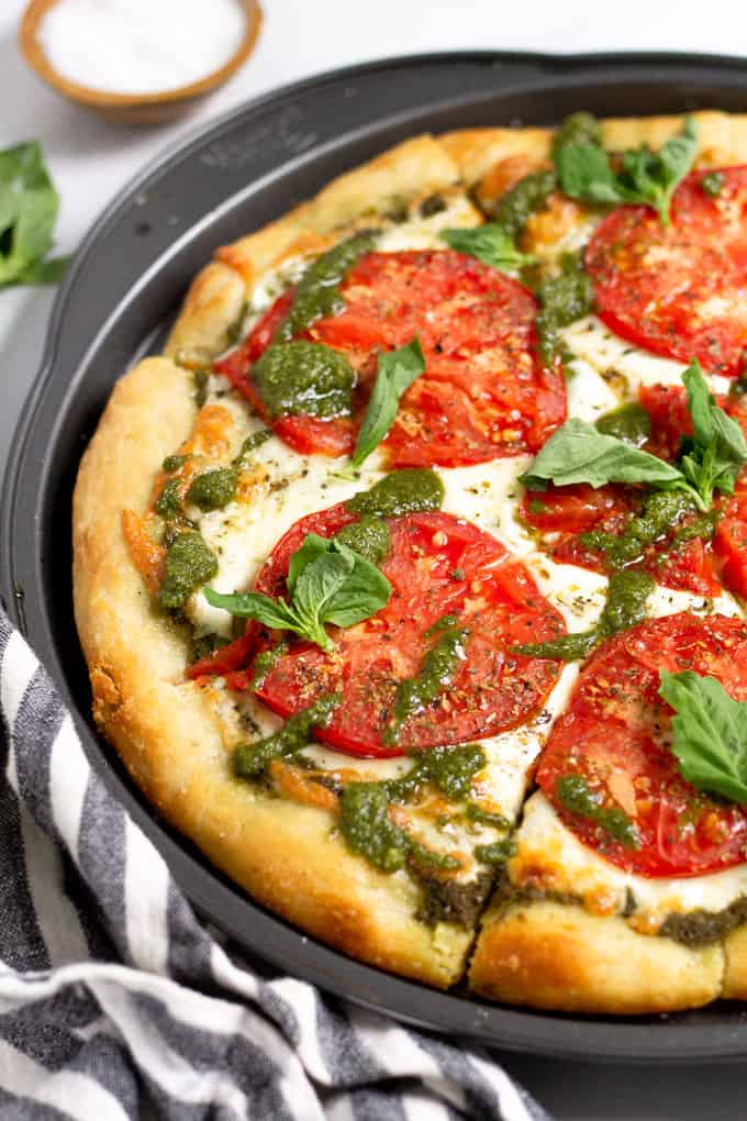 Close up shot of a pesto and tomato pizza drizzled with pesto sauce and garnished with fresh basil