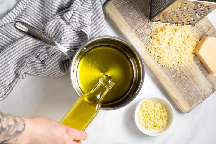 Hand pouring olive oil into a small sauce pan