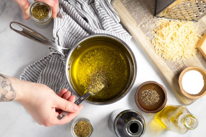 Hand adding dried herbs to a small saucepan of olive oil