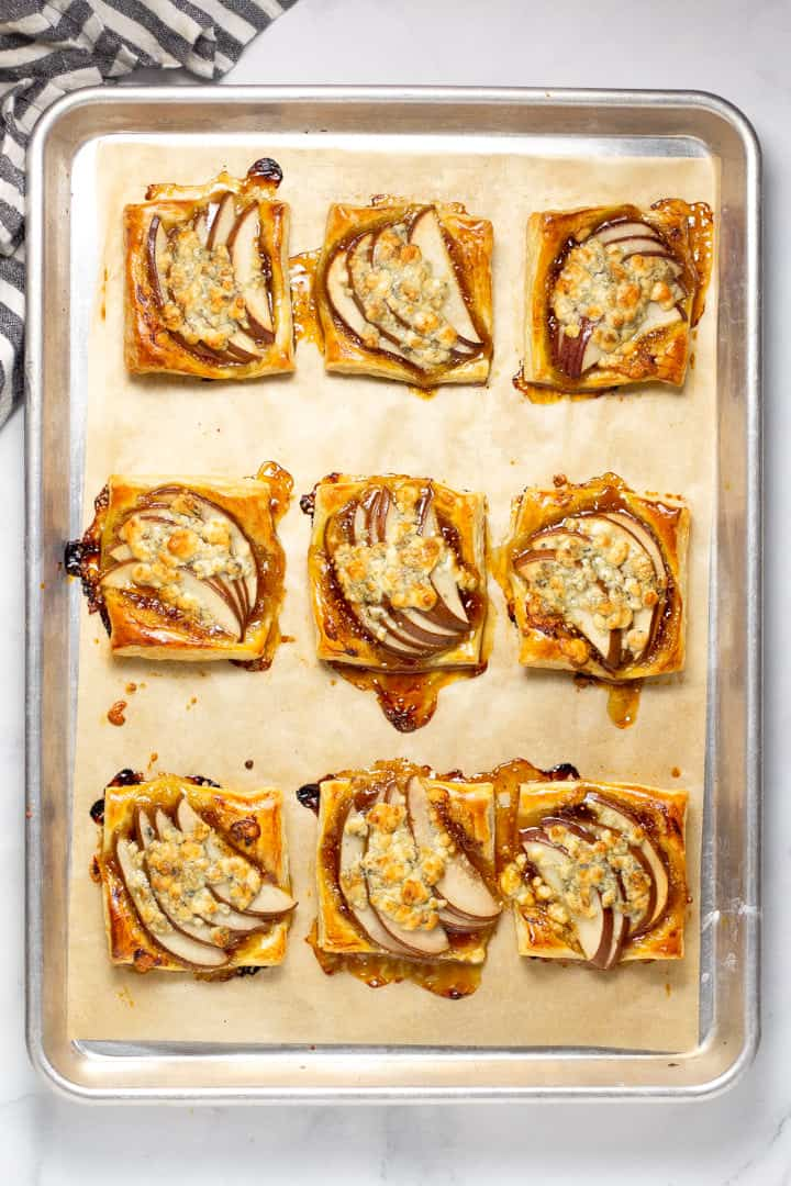 Parchment lined baking sheet with fresh baked square pear tarts