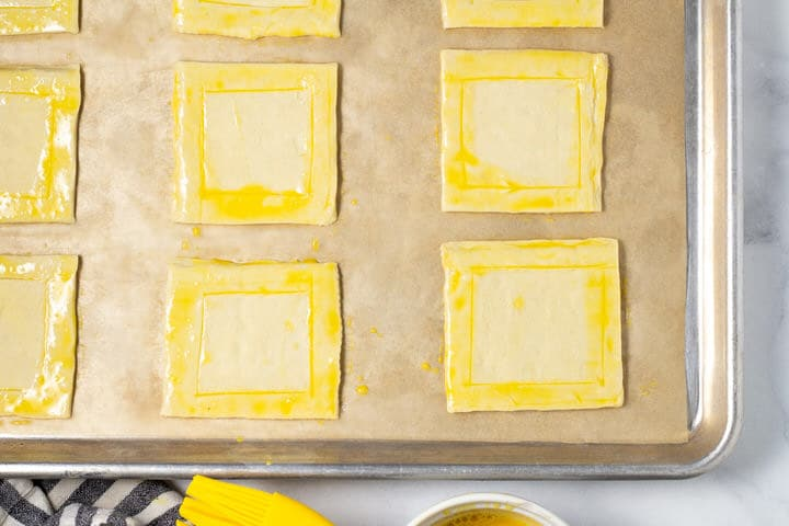 Puff pastry squares on a parchment lined baking sheet