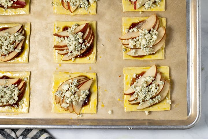 Puff pastry squares with fig jam pears and blue cheese on a parchment lined baking sheet