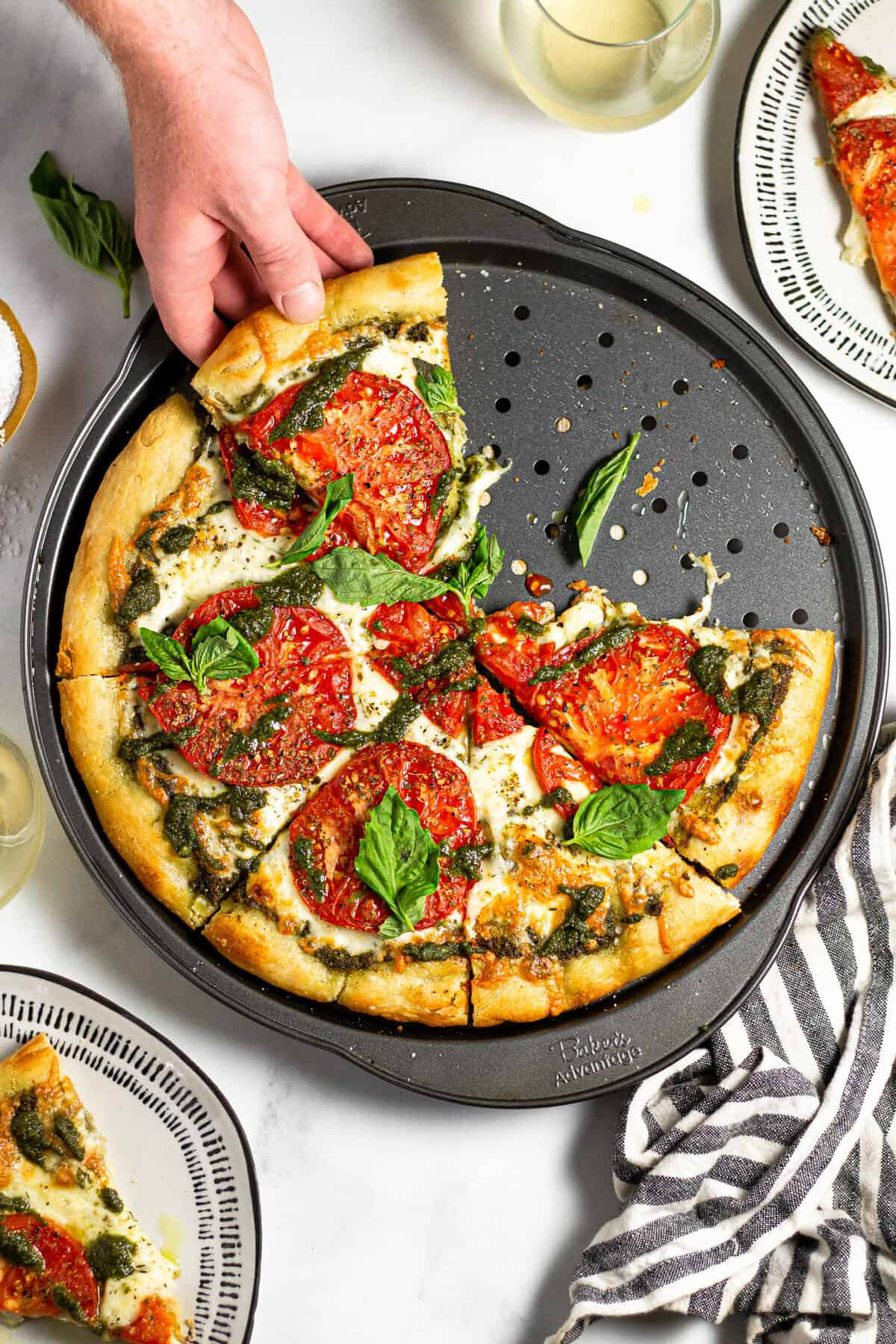 A hand reaching for a slice of pesto pizza on a pizza pan