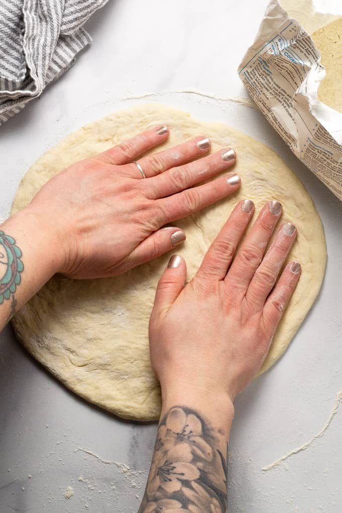 Pizza crust on a white marble counter top being stretched into a circle