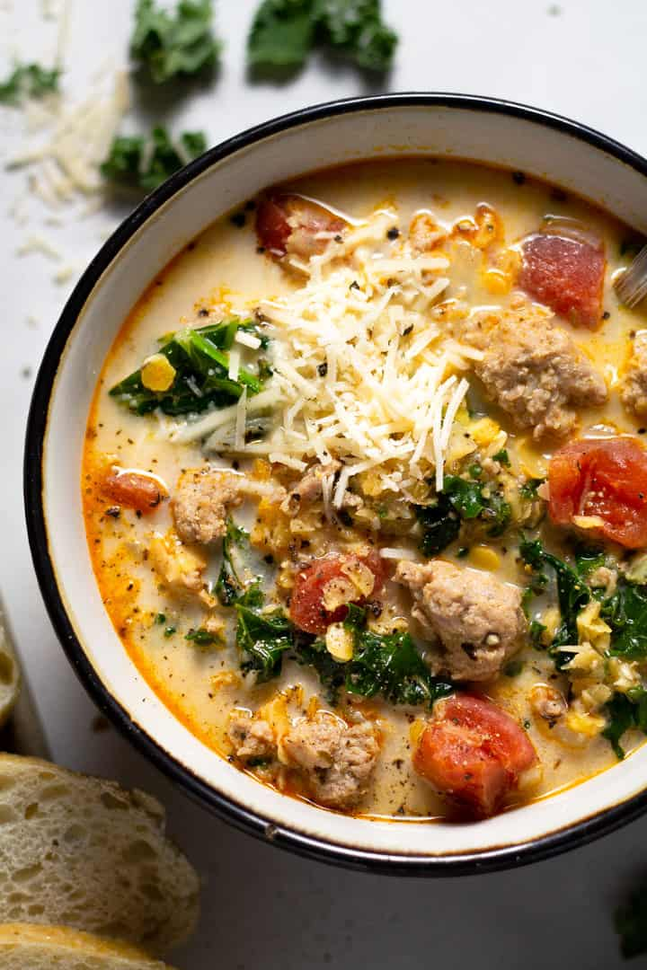 Overhead shot of a black and white bowl filled with sausage kale soup
