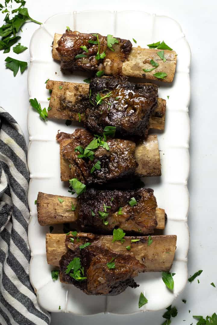 Overhead shot of a platter filled with short ribs garnished with fresh parsley