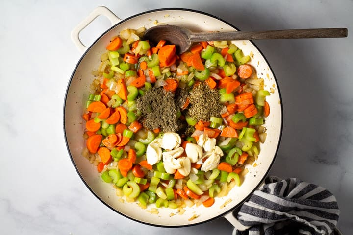 Large pot filled with carrots celery onion herbs and garlic