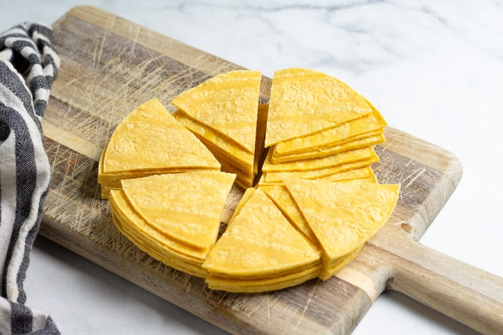 A brown cutting board with corn tortilla triangles on it