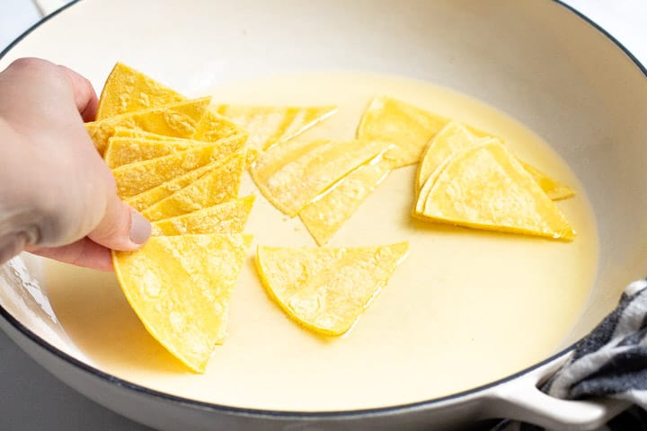 Corn tortilla triangles being added to a pot of shallow oil