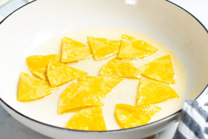Corn tortilla triangles cooking in a shallow pot of oil