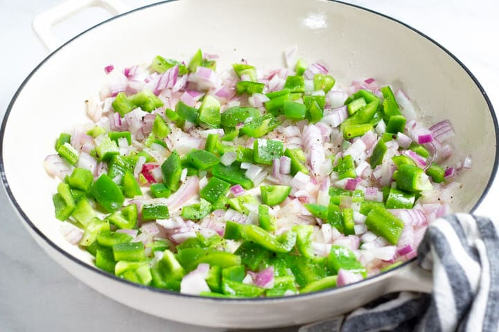 White saute pan filled with onion and green pepper