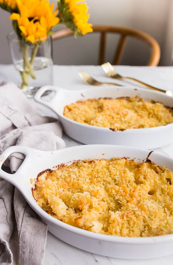 A table with two dishes of baked lobster mac and cheese