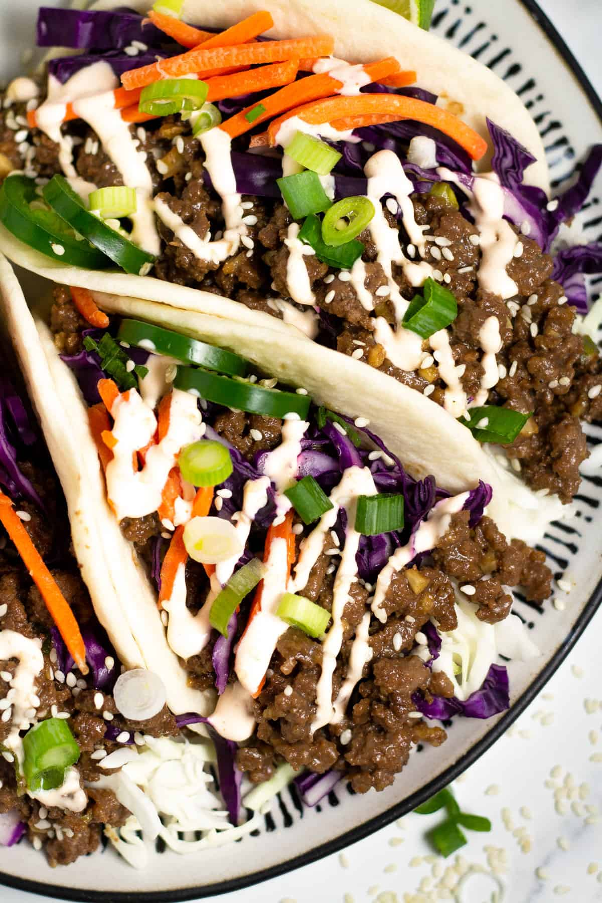 Overhead shot of a black and white plate filled with Korean beef tacos drizzled with spicy mayo.