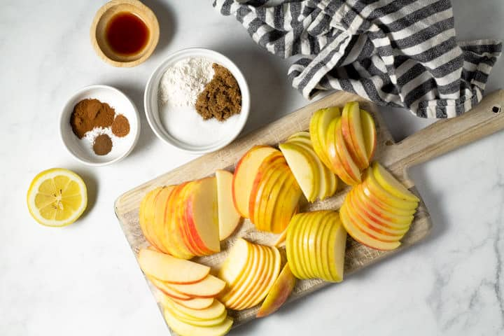 White marble counter top with a cutting board with sliced apples and small bowls of spices