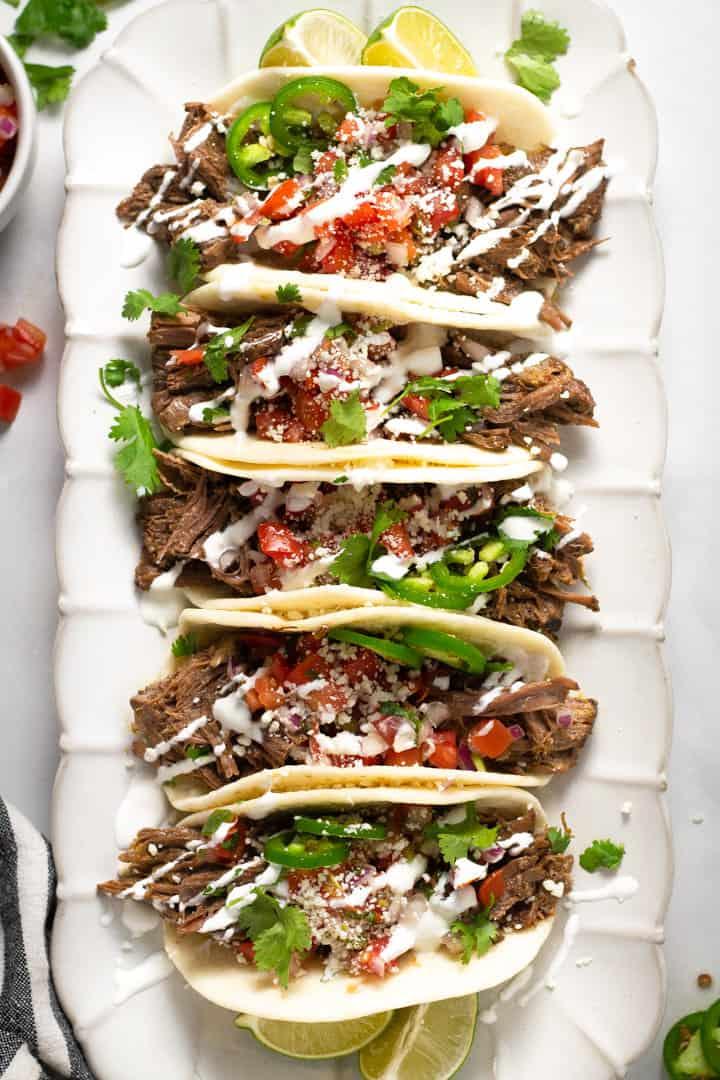 Overhead shot of a white platter filled with barbacoa beef tacos garnished with fresh cilantro