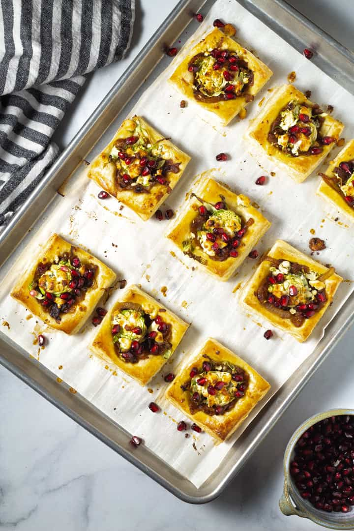 Parchment lined baking sheet with Brussels sprout tarts garnished with blue cheese and pomegranate seeds