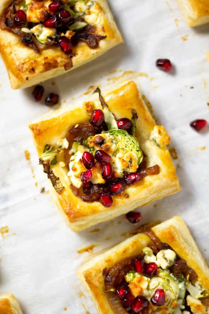 Close up shot of a Brussels sprout tart topped with pomegranate seeds